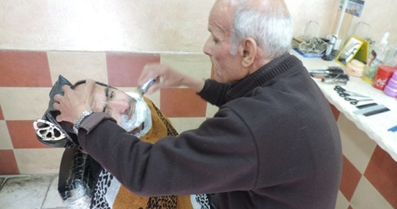 80-year-old Palestinian barber offers haircut and music